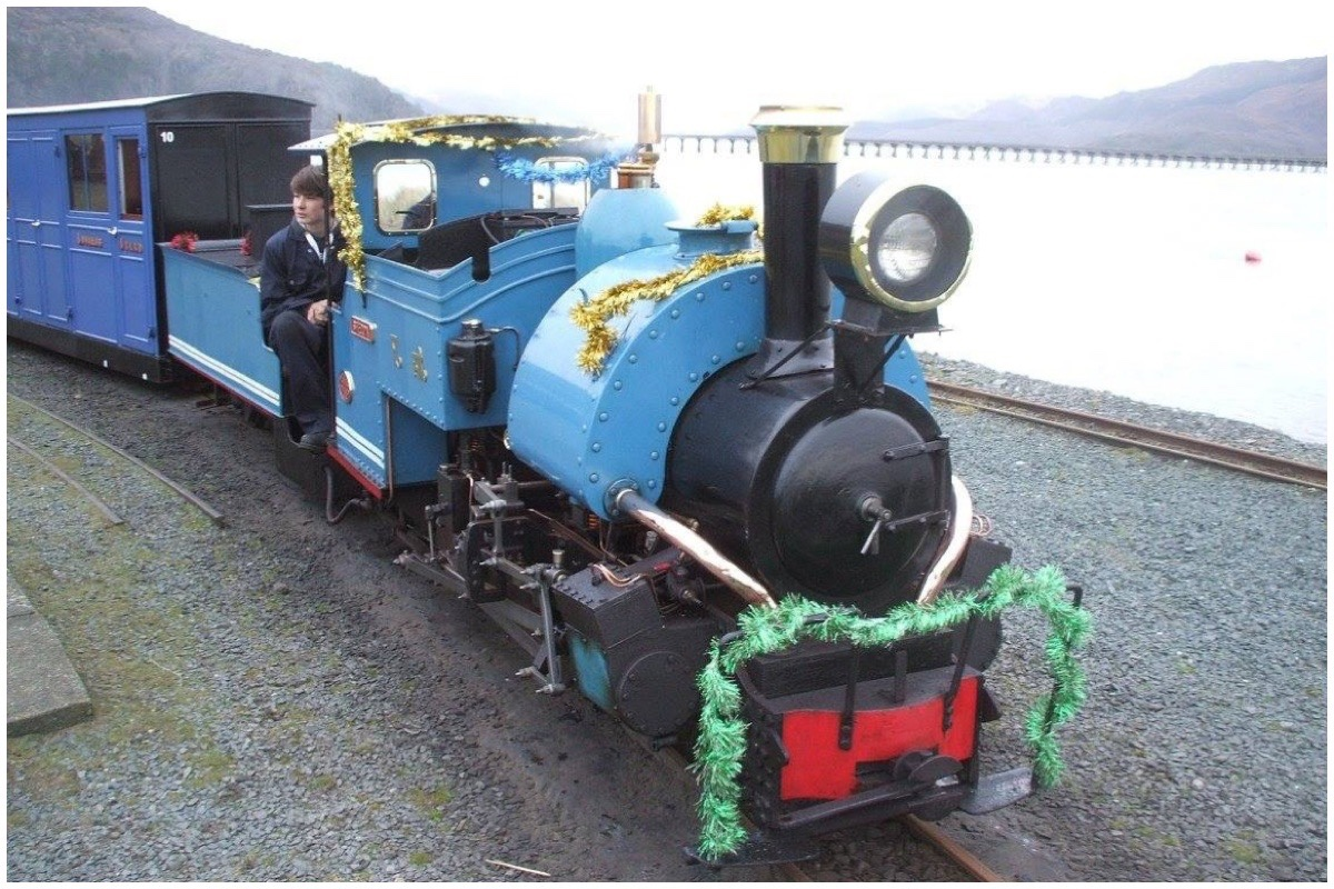 One of the Fairbourne locomotives decked out in tinsel with the Mawddach Estuary in the background