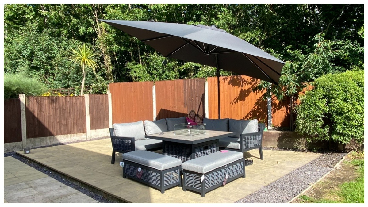 Garden furniture with the umbrella open. Trees in bakcground.