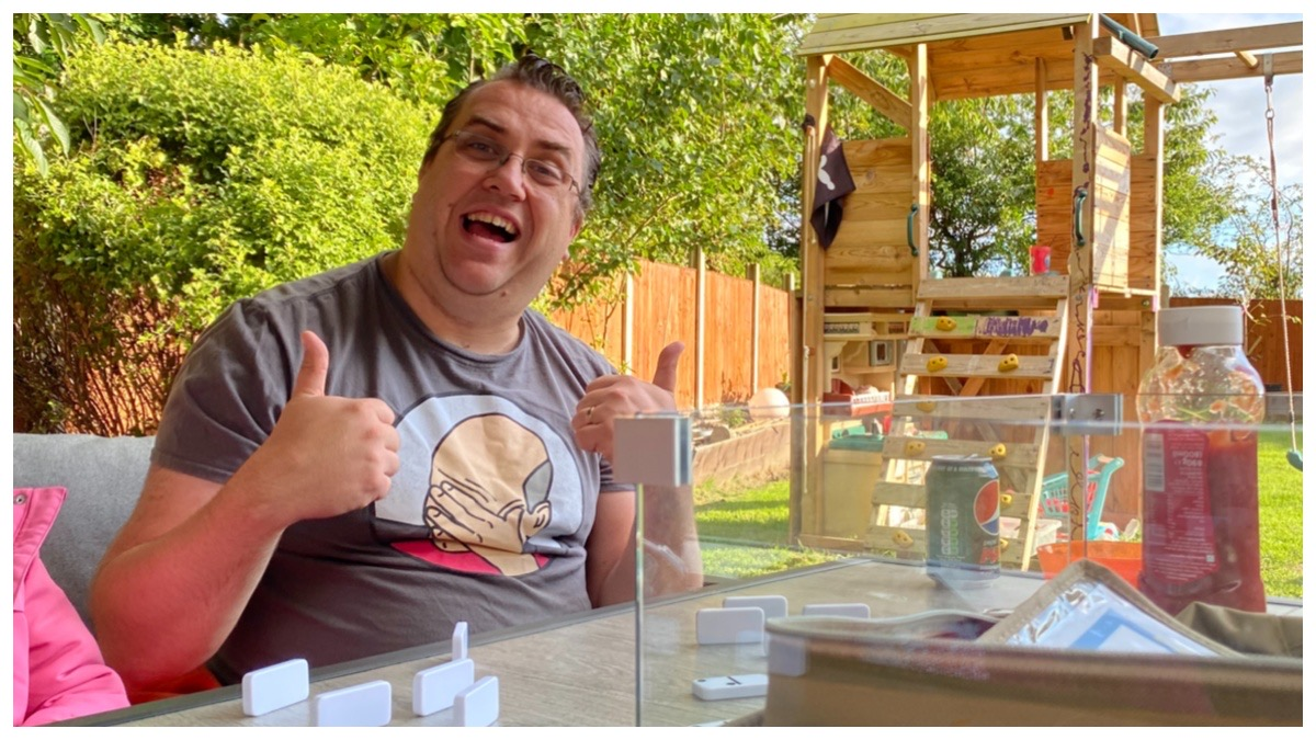 My husband giving the thumbs up whilst we play dominoes out in the garden