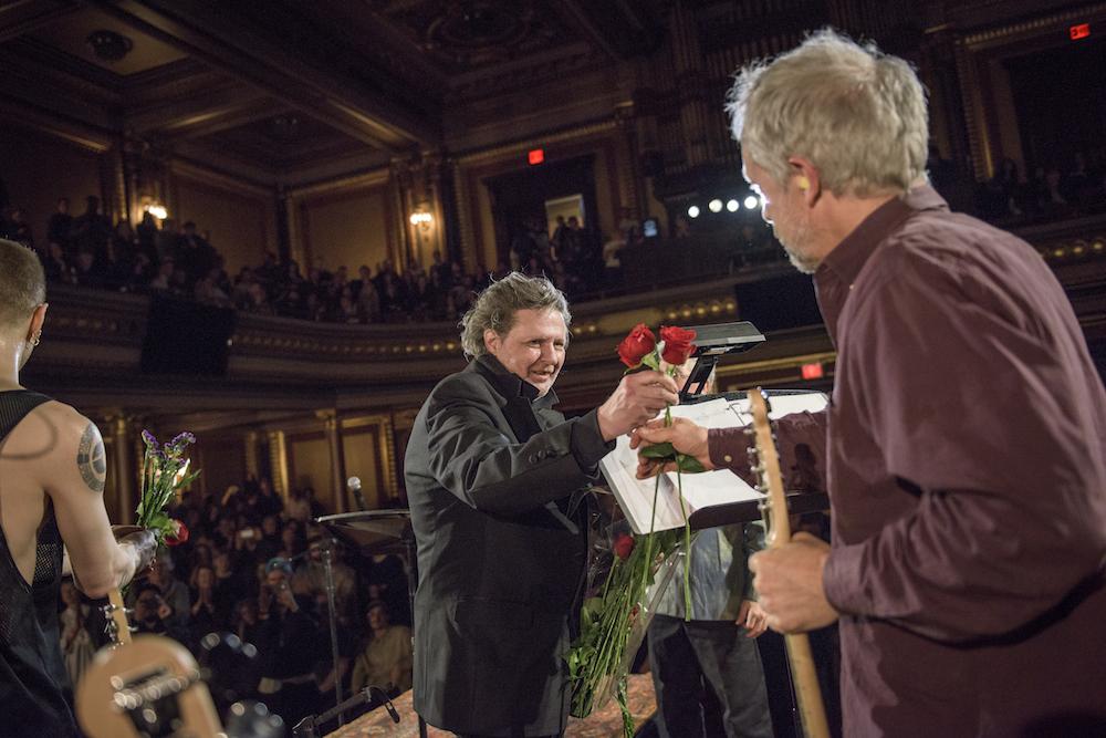 Glenn Branca hands out roses to the musicians taking part in Glenn Branca