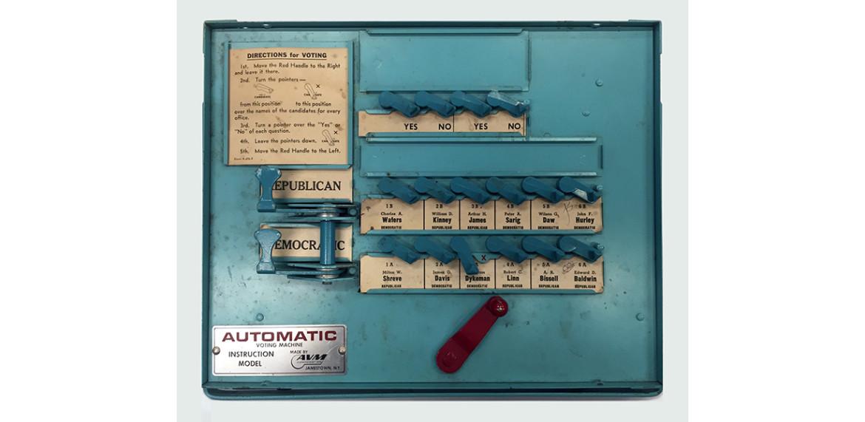 R. Luke DuBois Learning Machine #2, 2016 AVM voting machine (instruction model, blue, ca. 1955), voting booth, computer, camera, lights, screen