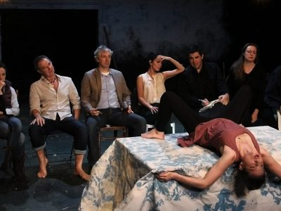 Image of Eight Actors looking embarassingly at another actor: a woman in a seagull pose splayed out on a table with her legs open