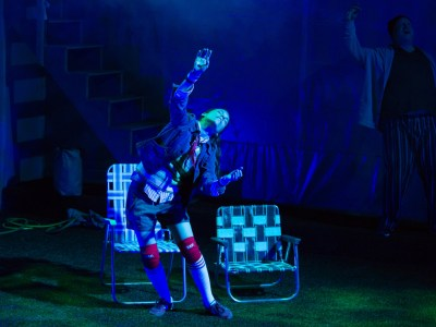 An actress dances in a blue spotlight, two lawn chairs are behind her.