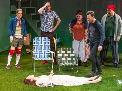 Four actors looking at (fifth actor) a woman in white dress lying in astro-turf with a toy arrow in her chest