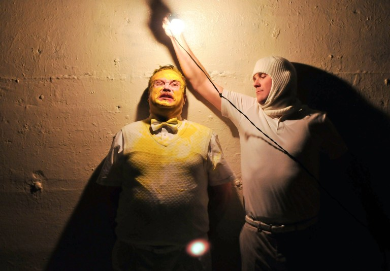 Two male actors, one covered in yellow paint, the other holding a lightbulb.