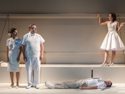 Five actors dressed in white in a surreal scene with one actor lying on the floor