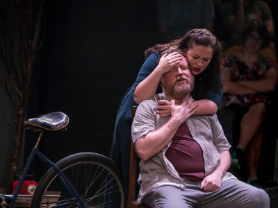 Two actors in a scene: A standing woman with a drink in her hand embracing a sitting man from behind him