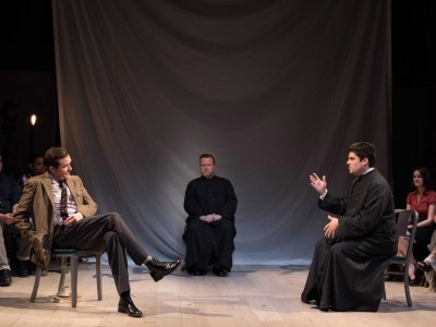 Three seated men, two dressed as priests, have a discussion. A scene from the play, Joan of Arc.