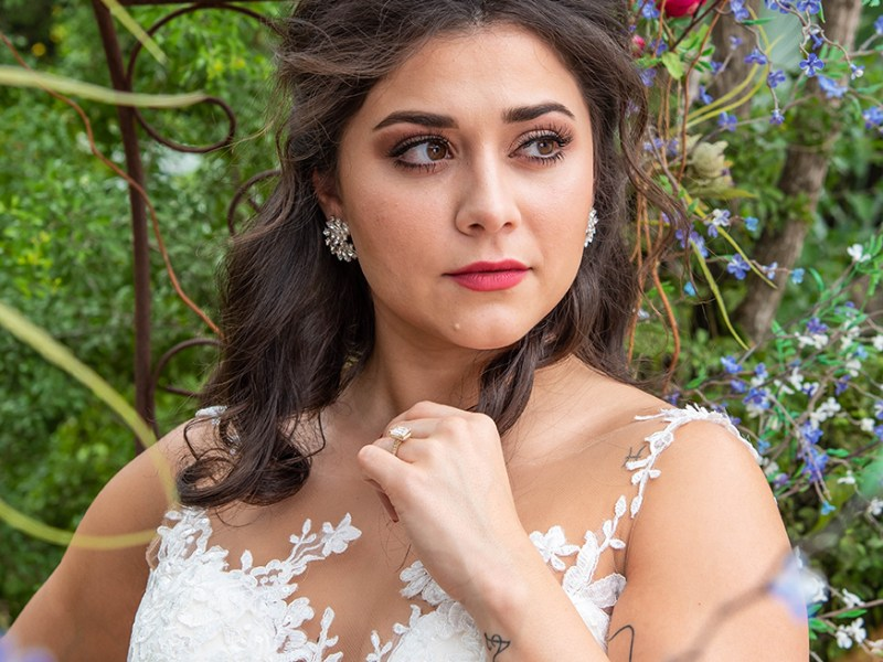 Framed by the colorful native flowers at the Bryan House in Mission Texas is a bride looking off into the distance with her gorgeous jewelry from Jared Jewelry on full display. Her hand twirls her gorgeous hair giving view to her beautiful wedding ring.