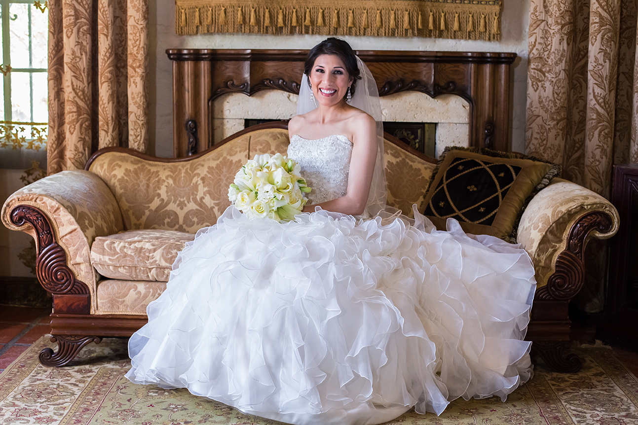 Bride smiling and sitting with bouquet at Quinta Mazatlan in McAllen, Texas.