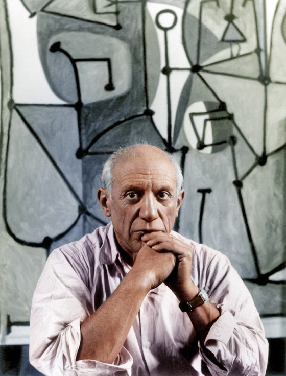 Pablo Picasso sits in front of his painting The Kitchen