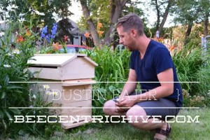 Dustin Bajer sitting in front of a Beecentric hive in Edmonton, Alberta, Canada