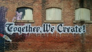 """""""Together We Create"""" Painted on a Brick Wall"""
