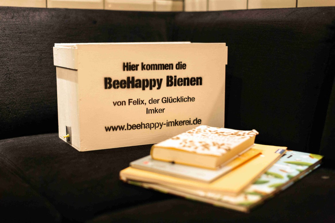 Die BeeHappy Bienenbox steht vor Bienenbüchern