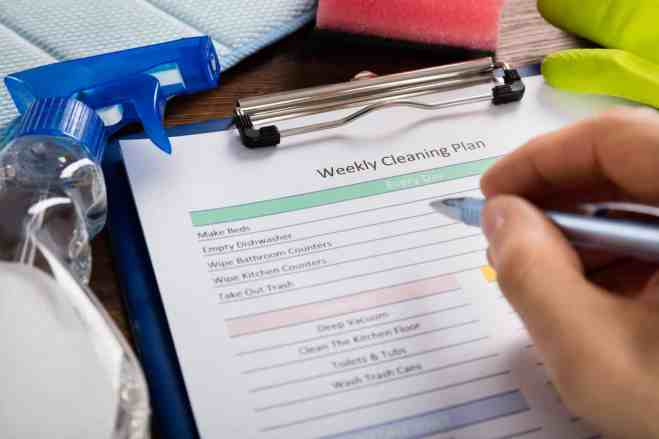 Close-up Of Person Hand Filling Weekly Cleaning Plan Form With Pen