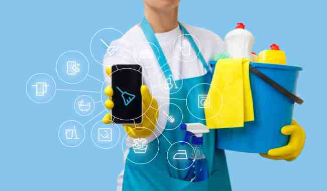 Man holding cleaning supplies and phone with cleaning app.