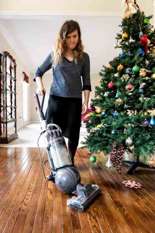 woman cleaning with vacuum cleaner hardwood floor from needles from Christmas tree in living room