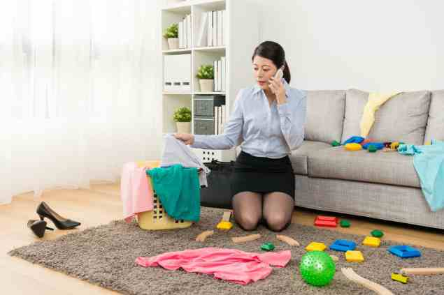 Lady manager using mobile cell phone calling with client when she after work kneeling down on living room floor sweeping messy toys with clothing.