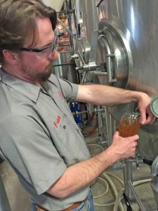 Franklin pulls a pint from the fermenting tank