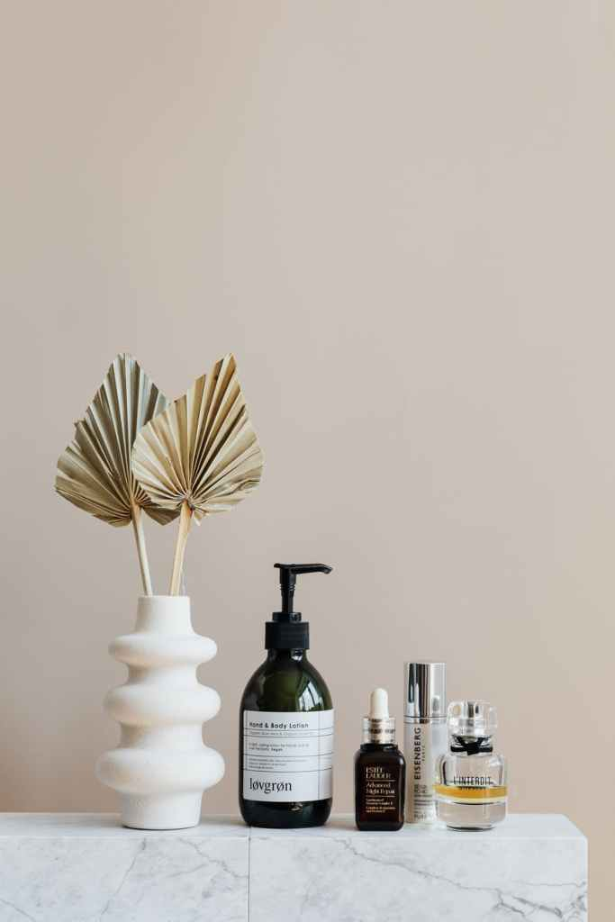set of cosmetic supplies near decorative leaves in vase on marble shelf
