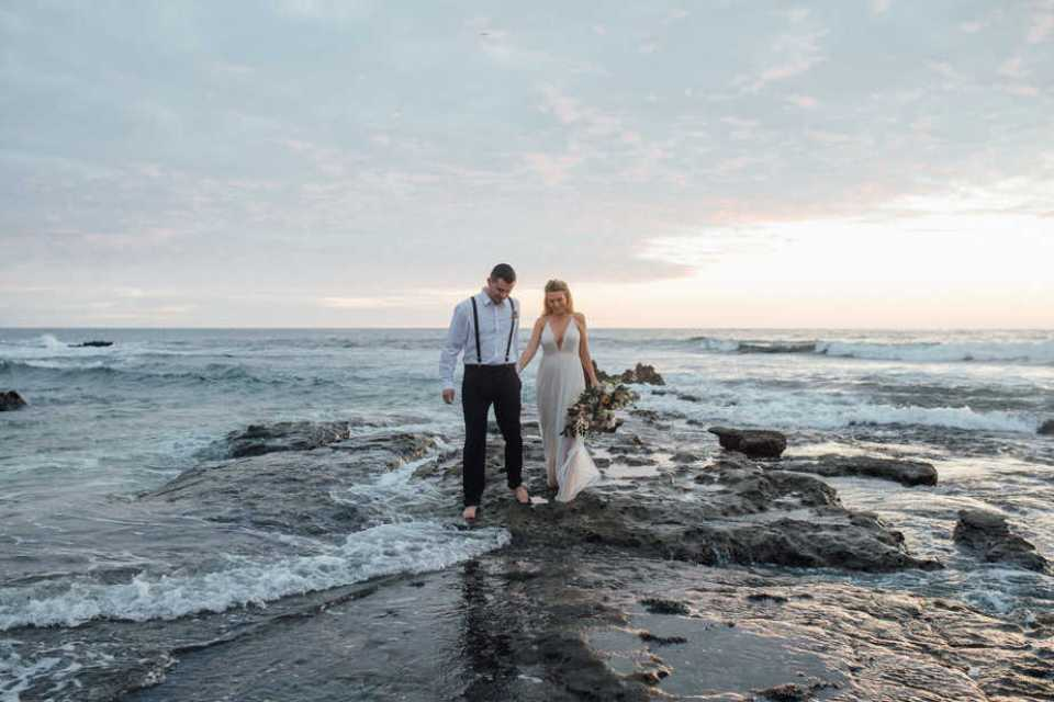 Sunset portrait of bride and groom during their beach elopement in San Diego, California.