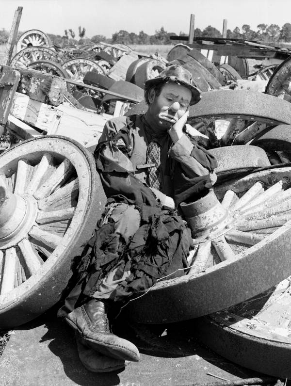 black and white photo of emmett kelly as weary willie, resting sadly on a pile of wagon wheels