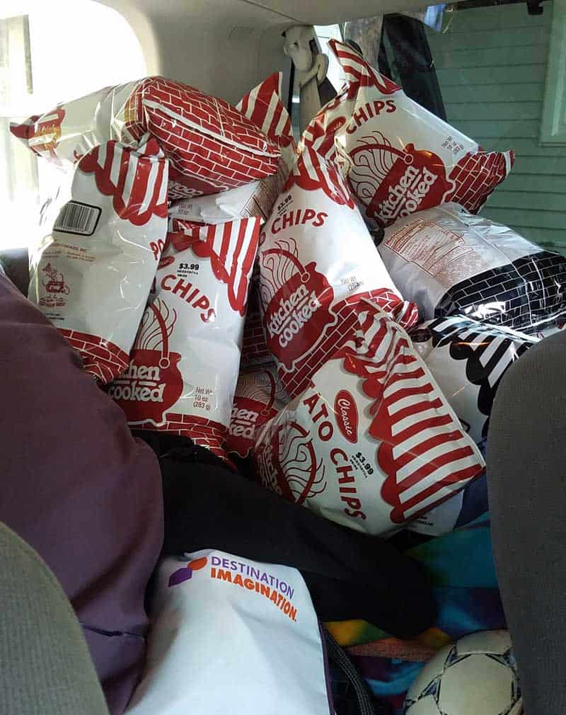 backseat of car is piled high with bags of kitchen cooked potato chips