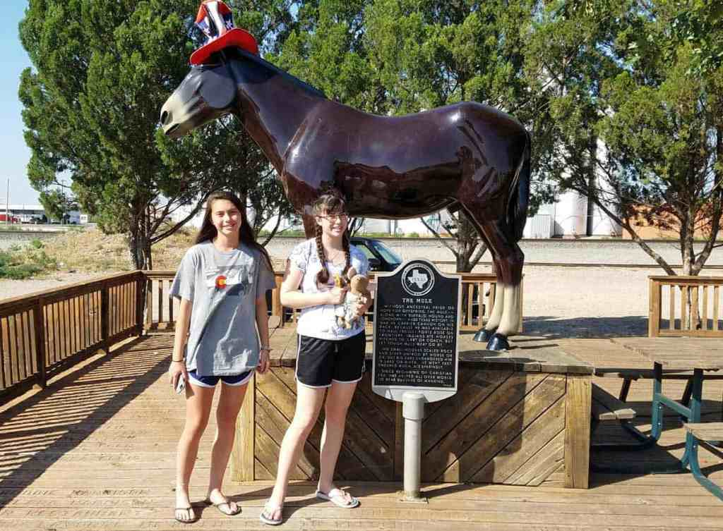 Two girls standing in front of a mule statue at the National Mule Memorial