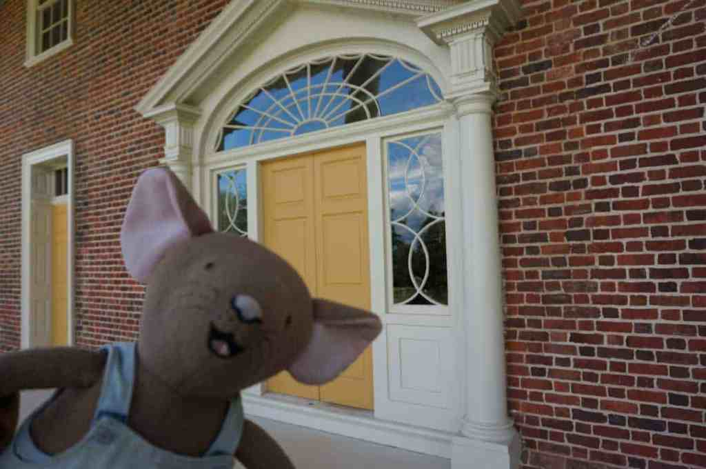 Travel mascot, Vacation Mouse, waits outside the yellow front door of Montepelier, home of President James Madison