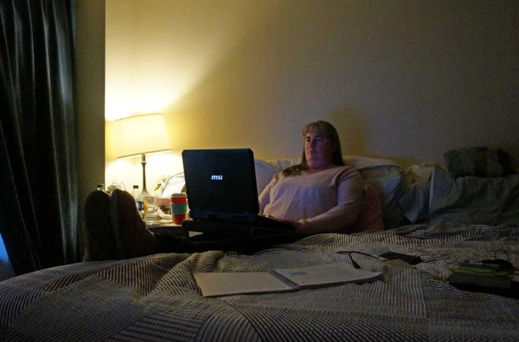 on bed with laptop, working