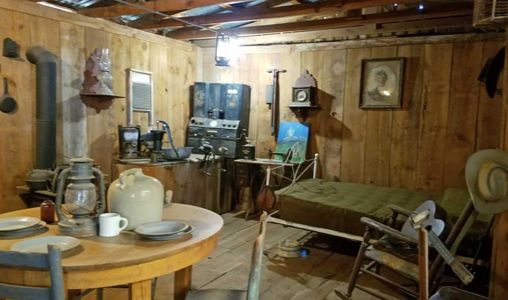 artifacts on display at Billy the Kid museum depicting an old cabin exterior