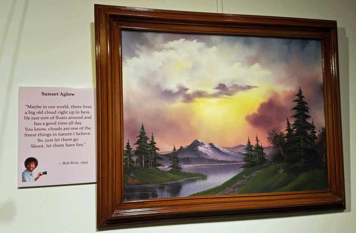 Bob Ross painting entitled Sunset Aglow features glowing clouds above a river and mountains