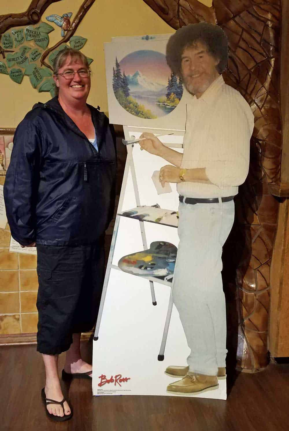 author is posing with a cardboard cutout of Bob Ross