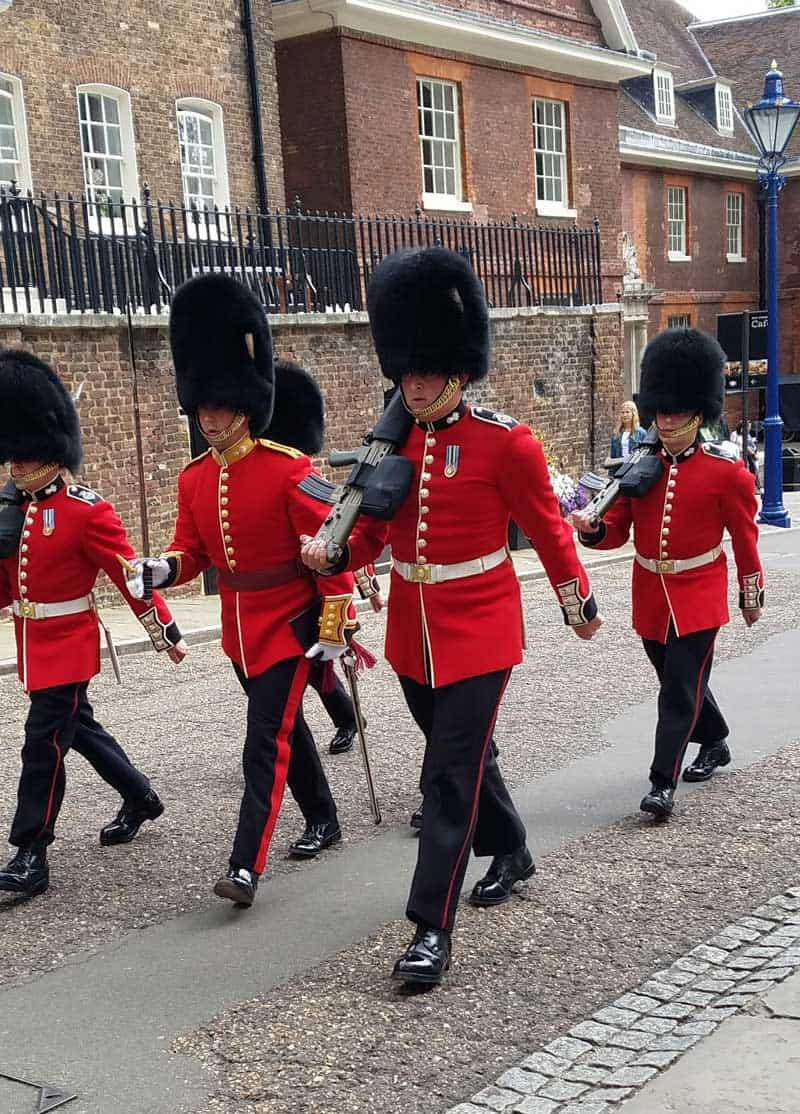 Guards in uniform at the Tower of London march in formation