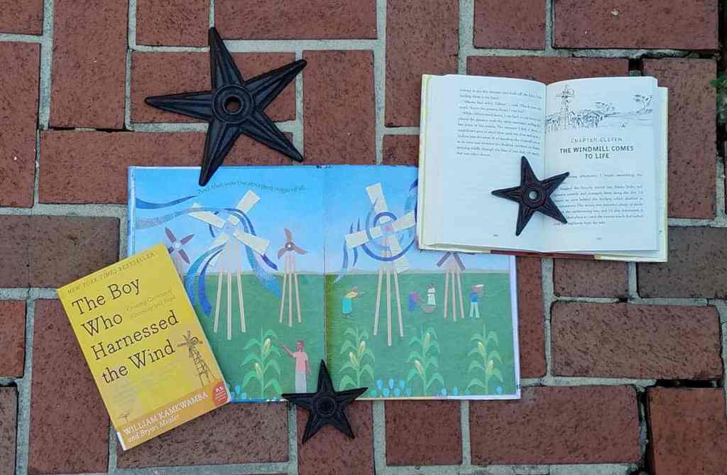 Three different copies of the book The Boy Who Harnessed the Wind spread across bricks, one book is open to show windmills illustration, another is open to show chapter title page