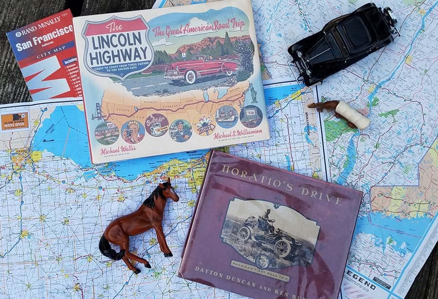 road maps with two books on top (horatio's drive and Lincoln highway) along with a toy horse, model car, and toy pioneer wagon