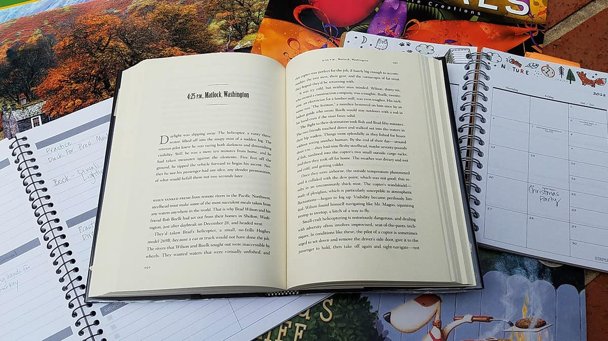 a book is open to a page titled 4:25 p.m. Matlock, Washington. In the background are several wall calendars and planners to support the theme of the book titled One Day.