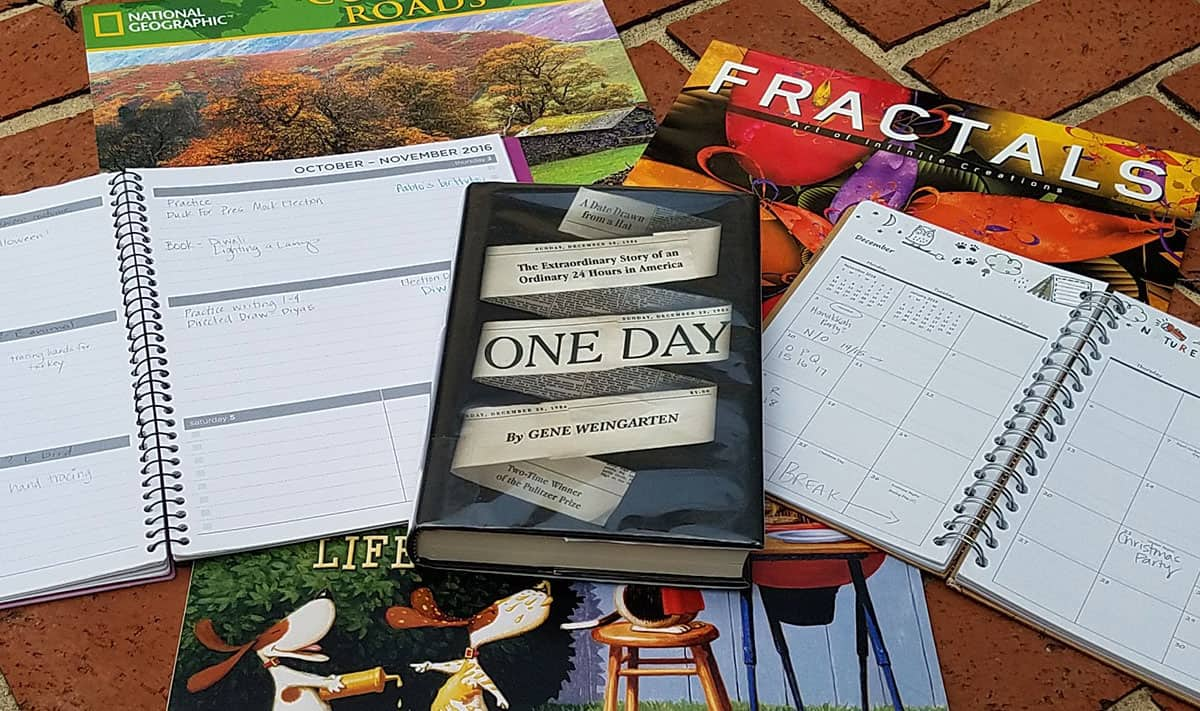 A book, titled One Day: The Extraordinary Story of an Ordinary 24 Hours in America, displayed on a backdrop of planners and wall calendars.
