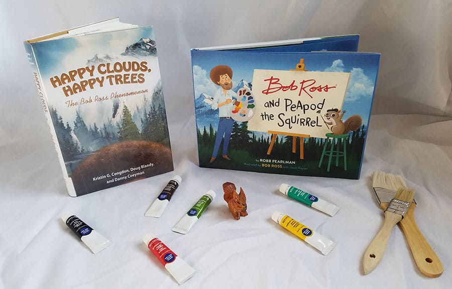 paint and brushes in front of two books title Happy Clouds, Happy Trees The Bob Ross Phenomenon and Bob Ross and Peapod the Squirrel