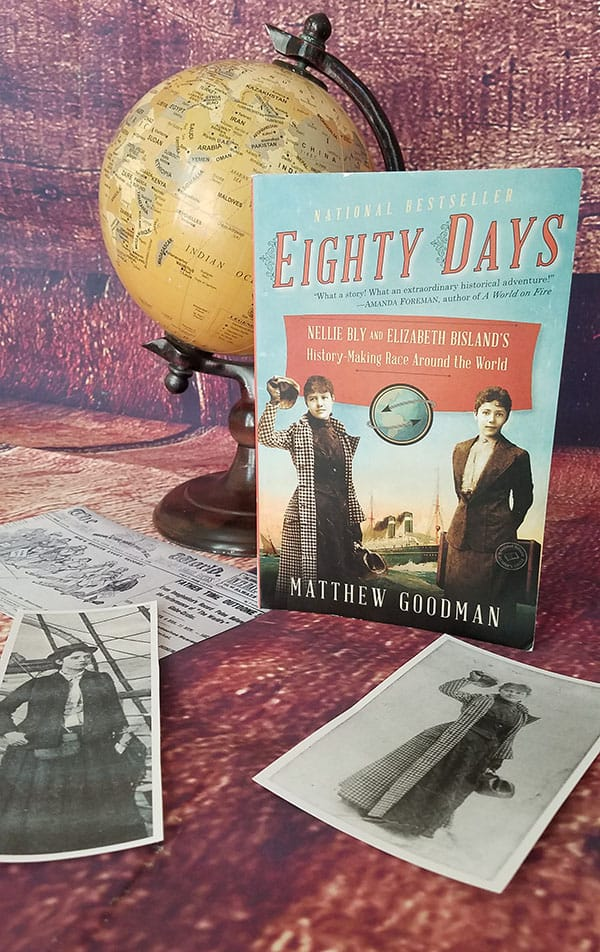 Book: Eighty Days by Matthew Goodman with a globe and printed photos of nellie bly and elizabeth bisland