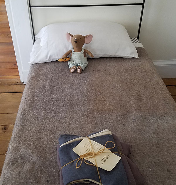 stuffed mouse sitting on cot with wool blanket