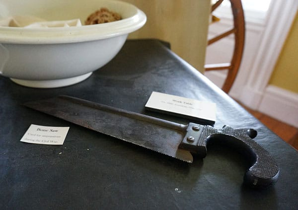 bone saw used in Civil War on table with bowl and sponges