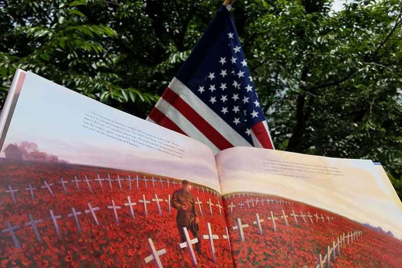 open book showing painting of white crosses surrounded by red poppies and one soldier stands reflectively in the center