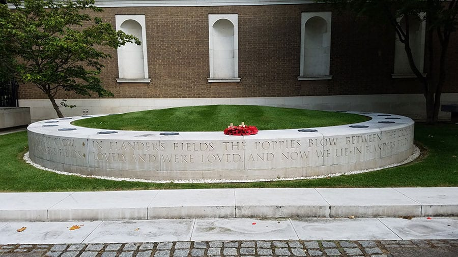 round concrete ring with grass in center and ring of poppies on the front edge. Engraved words of In Flanders Fields poem on side