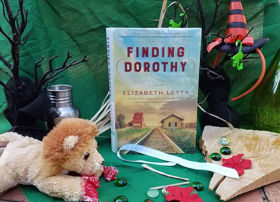 Cover of book, Finding Dorothy by Elizabeth Letts, is surrounded by stuffed lion, blue gingham ribbon, spooky trees, and red gems against an emerald green background