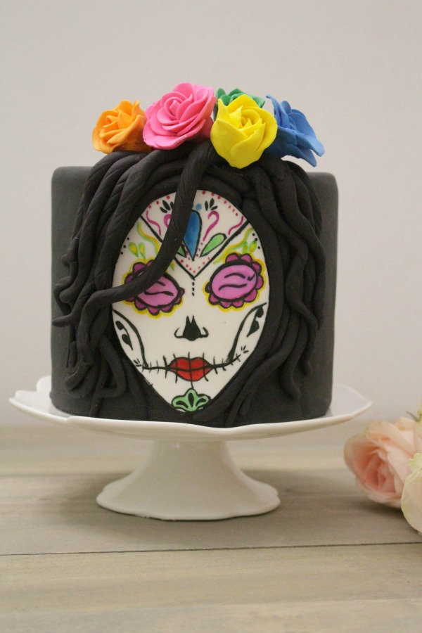 Behind the cake-Cake covered in black fondant with a sugar skull face painted in watercolors with sugar flowers