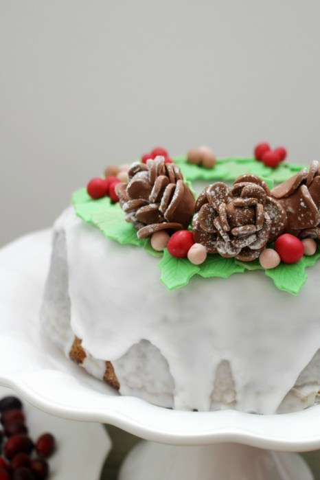 Behind the cake - Christmas bundt cake decorated with green mistletoe leafs made out of fondant, pine cones and berries.