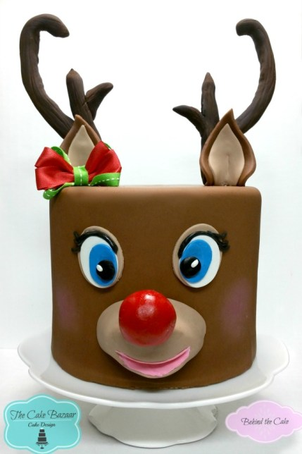 Behind the cake - Cake decorated with fondant as a reindeer cake with molded antlers and red nose
