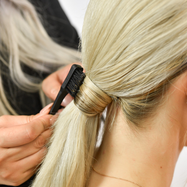 Erase Flyaways On A low Ponytail With A Small Toothbrush-like Brush And Finishing Spray