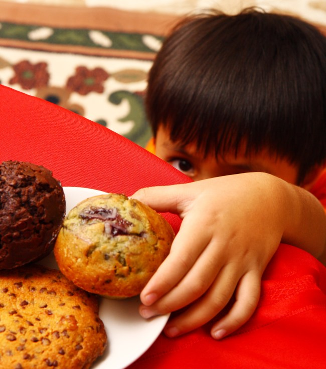 Naughty Kid Taking One Of His Mother's Cakes On The Table